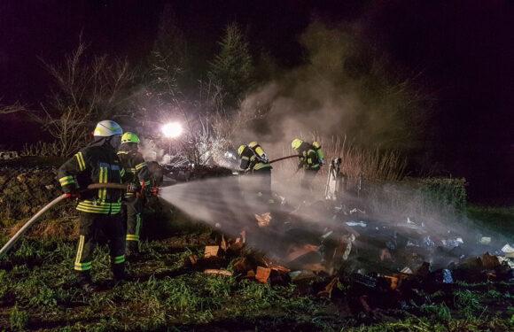 Feuerwehr löscht brennenden Holzhaufen in Scheie